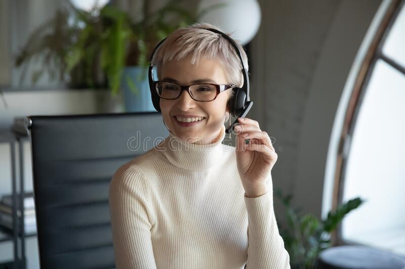 Smiling businesswoman consult client online on laptop. Smiling middle-aged businesswoman in glasses and headset working on laptop in office talk with colleague royalty free stock photography