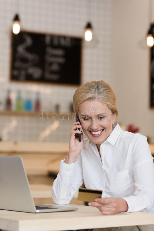Smiling businesswoman with credit card in hand talking on smartphone while sitting at table with laptop. In cafe stock images