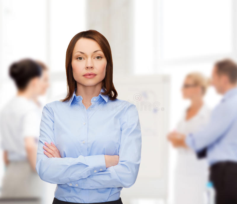 Smiling businesswoman with crossed arms at office stock images