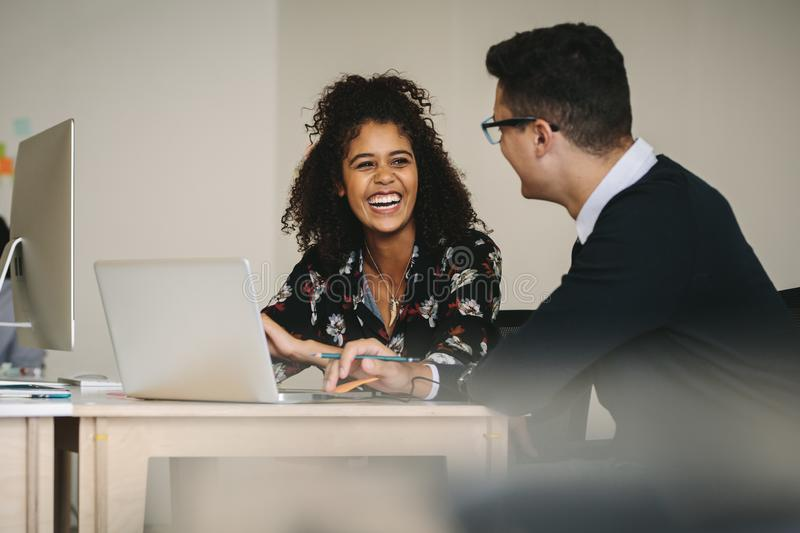 Smiling businesswoman discussing work with colleague in office royalty free stock images