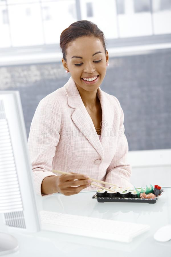 Smiling businesswoman eating at desk. Smiling businesswoman eating sushi at desk in lunch time royalty free stock image