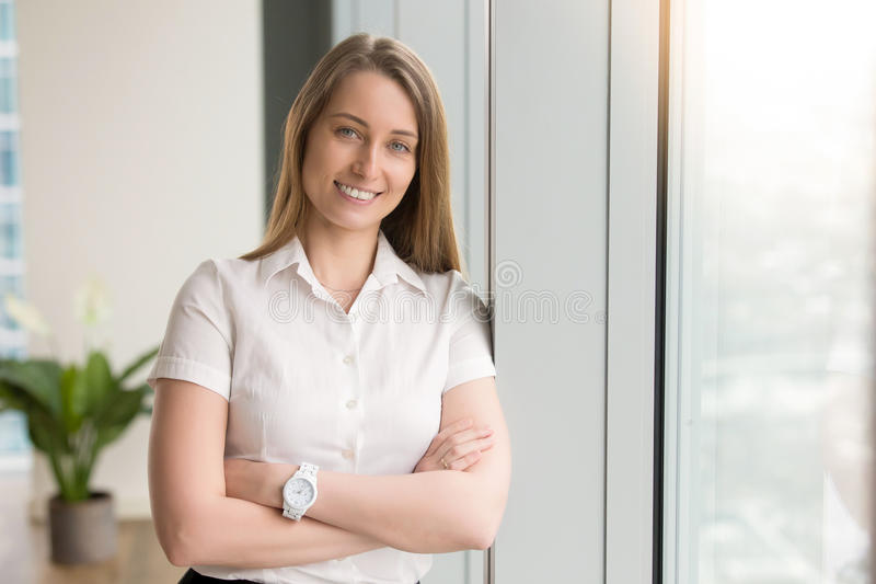 Smiling businesswoman feeling optimistic at office. Head shot portrait of smiling attractive young woman with arms crossed looking at camera. Successful positive royalty free stock photo
