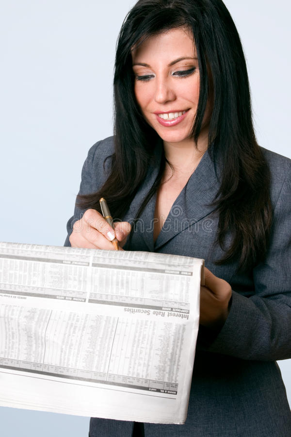 Smiling businesswoman finance newspaper. A smiling business woman checking the finance, bonds, shares, securities, pages of a national newspaper. Company data royalty free stock images
