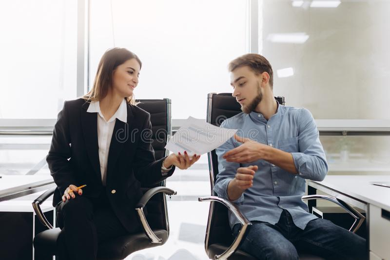 Smiling businesswoman giving papers to someone in office. On documents stock image
