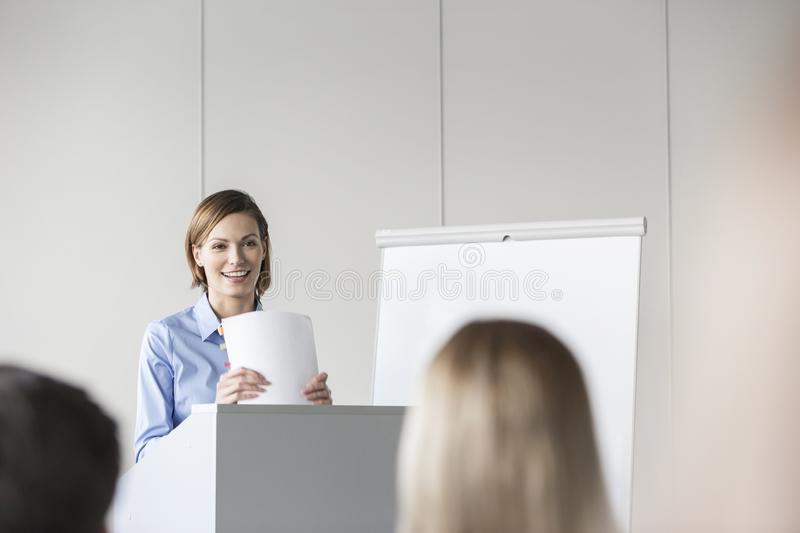 Smiling businesswoman giving presentation to colleagues in conference stock images