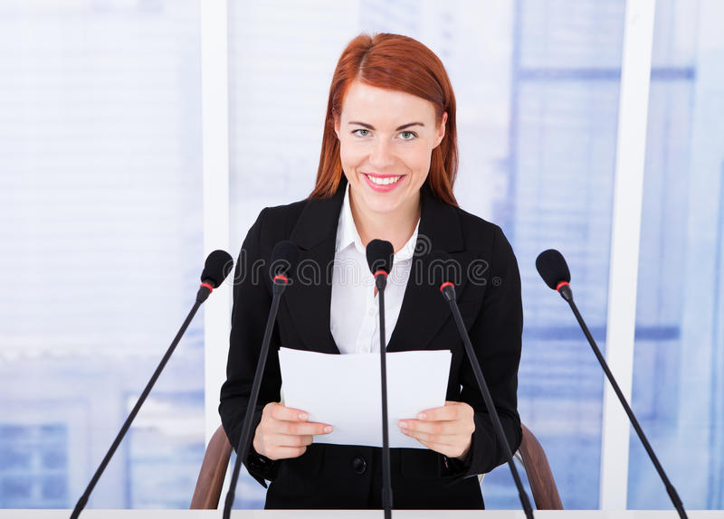 Smiling businesswoman giving speech at conference stock photo