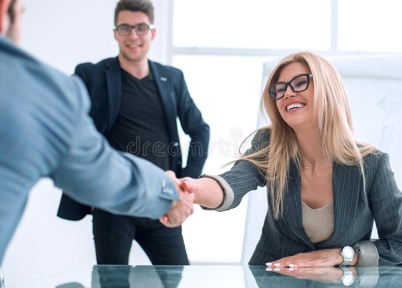 Smiling businesswoman greeting business partner with a handshake. royalty free stock images