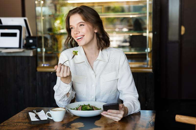 Smiling businesswoman having lucnch at the cafe indoors royalty free stock images