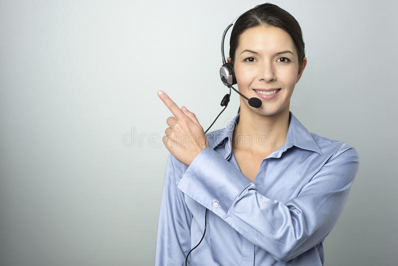 Smiling businesswoman with a headset pointing stock photos