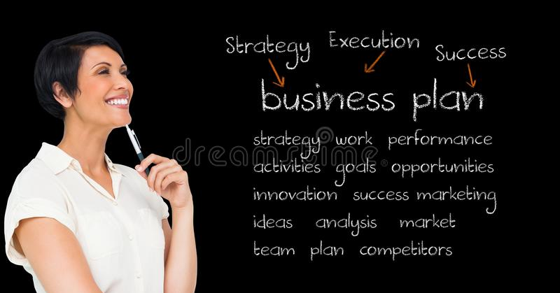 Smiling businesswoman holding pen and standing against blackboard with business terms stock photos