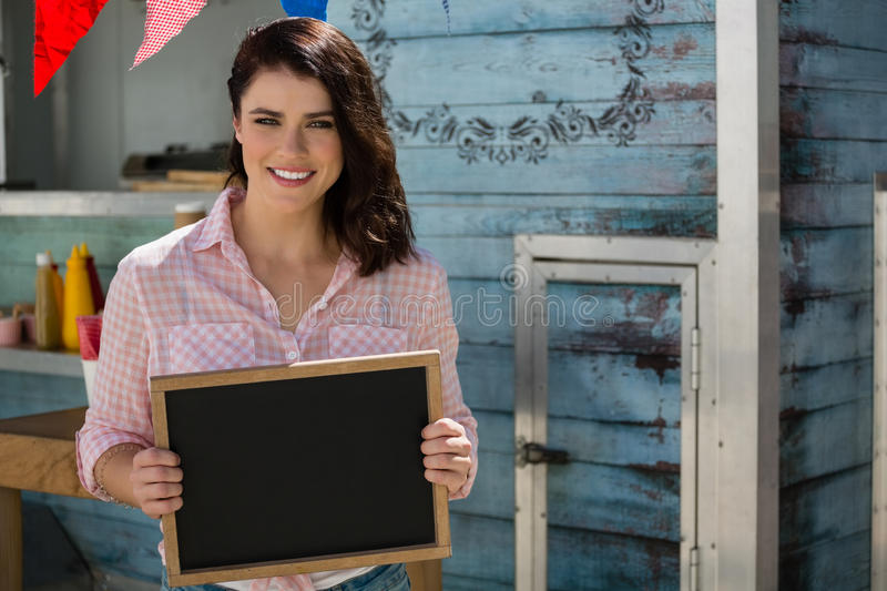 Smiling businesswoman holding writing slate while standing by food truck royalty free stock image
