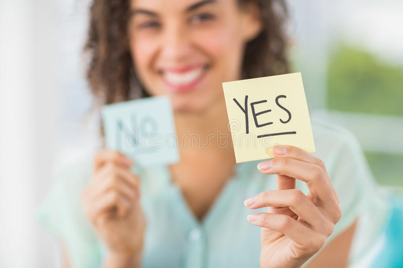 Smiling businesswoman holding yes and no sticks royalty free stock photos