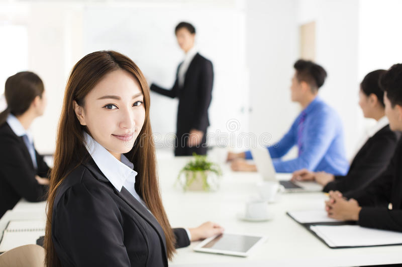 Smiling businesswoman looking at camera with colleague royalty free stock images