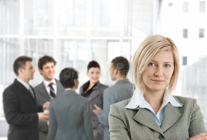 Smiling businesswoman in office lobby. Colleagues talking in background stock photos