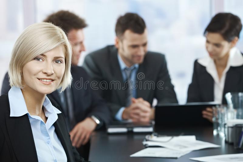 Smiling businesswoman portrait at meeting. Portrait of mid-adult businesswoman smiling at camera with colleagues at meeting in background stock photo