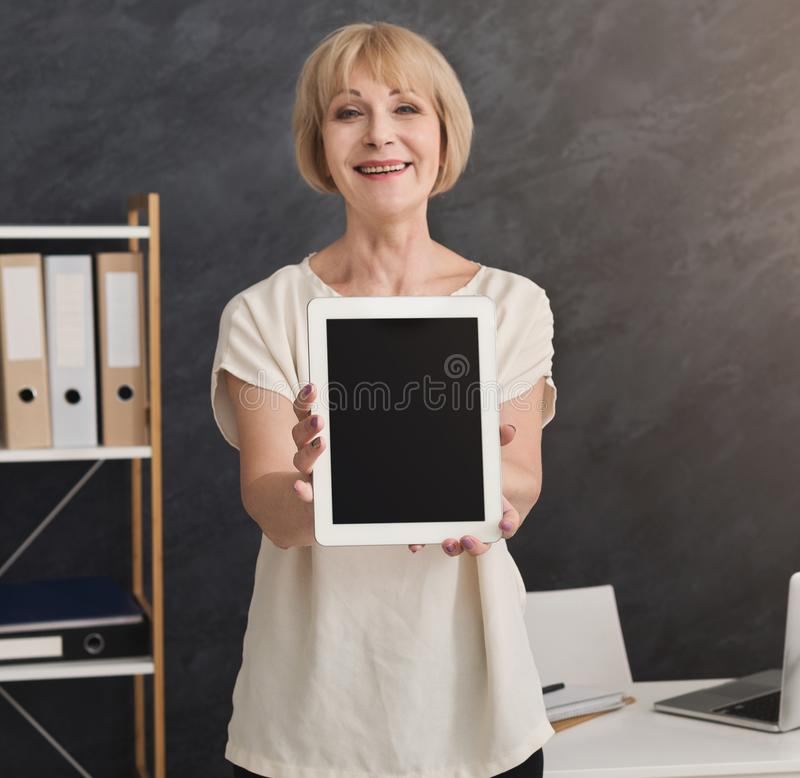 Smiling businesswoman presenting digital tablet with blank screen for advertisement royalty free stock image