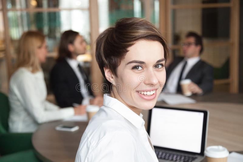 Smiling businesswoman professional interpreter looking at camera. Ambitious attractive smiling young businesswoman looking at camera at group meeting, happy royalty free stock image