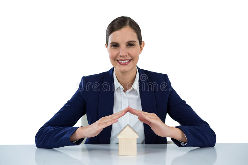 Smiling businesswoman protecting house model with hands stock image