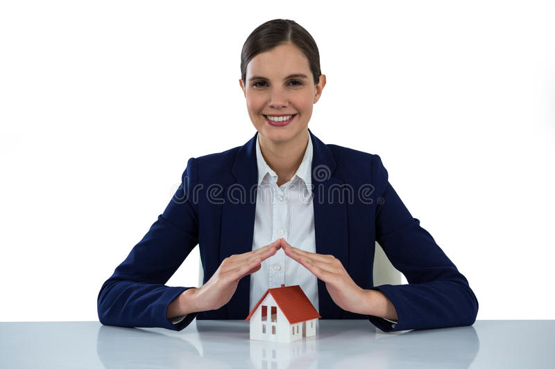 Smiling businesswoman protecting house model with hands stock images