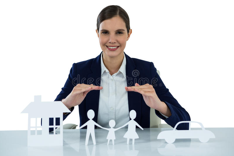 Smiling businesswoman protecting paper cut out family, house and car with hands. Portrait of smiling businesswoman protecting paper cut out family, house and car stock photos