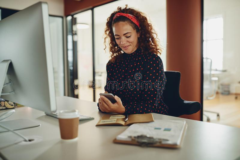 Smiling businesswoman reading a text message at her office desk stock images
