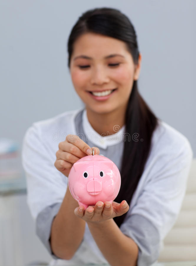 Smiling businesswoman saving money in a piggybank stock images