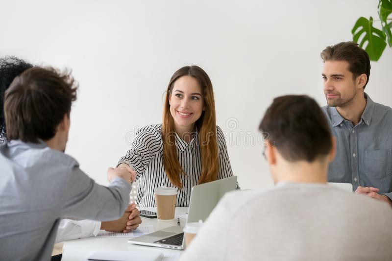 Smiling businesswoman shaking hand of male partner at group meet. Smiling businesswoman shaking hand of male partner at negotiations, friendly women handshaking royalty free stock photos