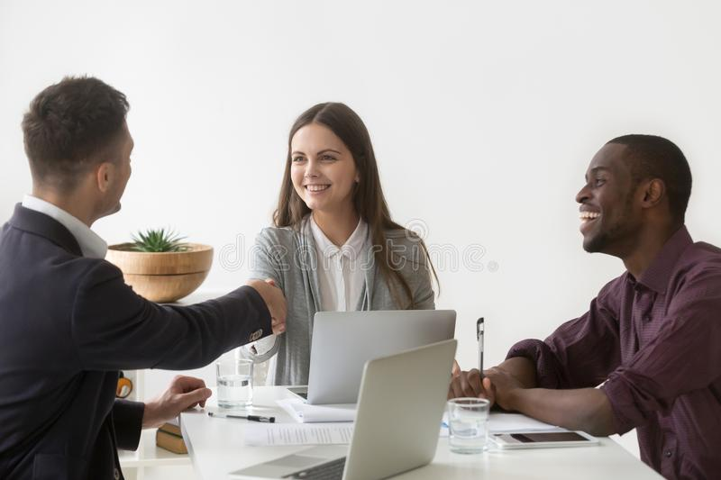 Smiling businesswoman shaking hand of male partner at group meet. Smiling millennial businesswoman shaking hand of male partner at diverse group negotiation royalty free stock photos