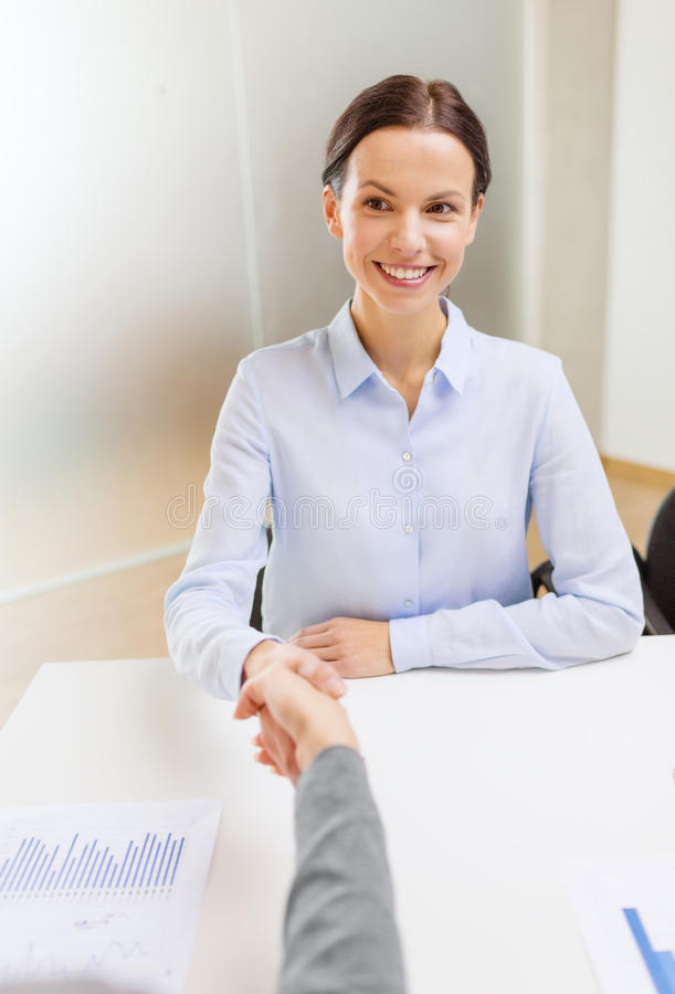 Smiling businesswoman shaking hand in office royalty free stock images