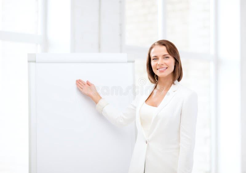 Smiling businesswoman showing flipchart. Business and education concept - smiling businesswoman showing flipchart stock photos