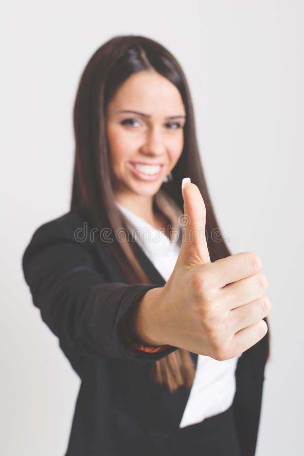 Smiling businesswoman showing thumb up. Attractive young Caucasian smiling businesswoman showing thumb up. Selective focus on thumb, model blurred in background stock image