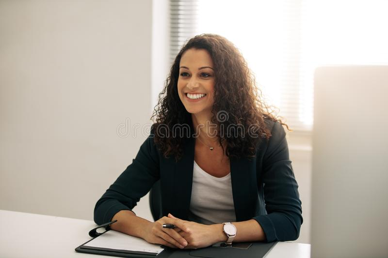 Smiling businesswoman sitting at her desk in office stock photos