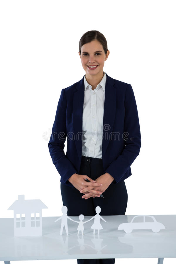 Smiling businesswoman standing with paper cut out of family, house and car on table royalty free stock images
