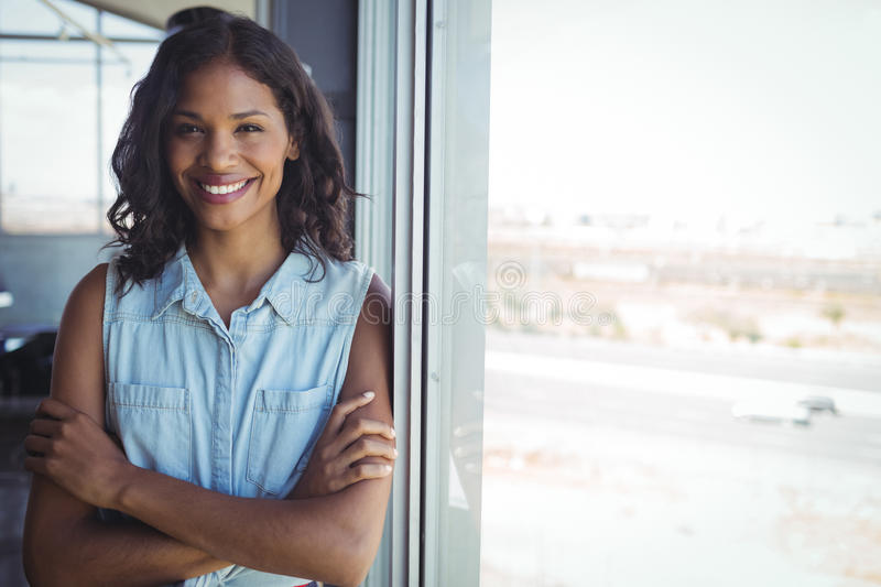 Smiling businesswoman standing by window in office royalty free stock photo