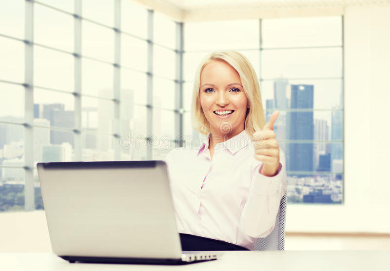 Smiling businesswoman or student with laptop. Business, people, success, gesture and technology concept - smiling businesswoman or student showing thumbs up with stock photo