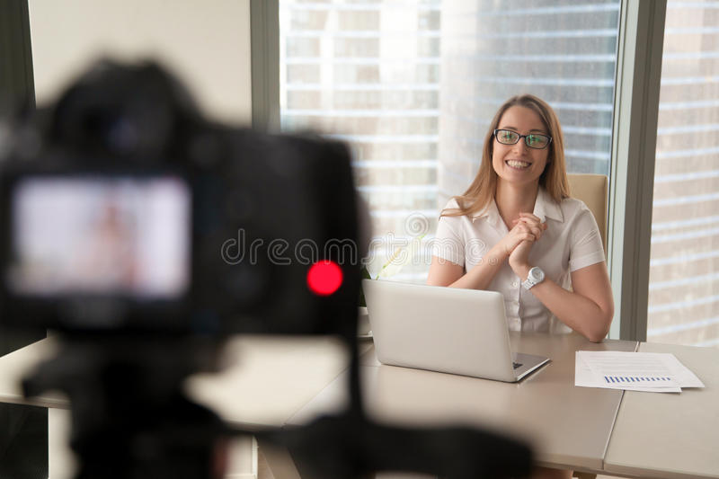 Smiling businesswoman talking on camera, lady recording business. Smiling businesswoman talking on camera, happy entrepreneur vlogger recording business vlog at stock photo