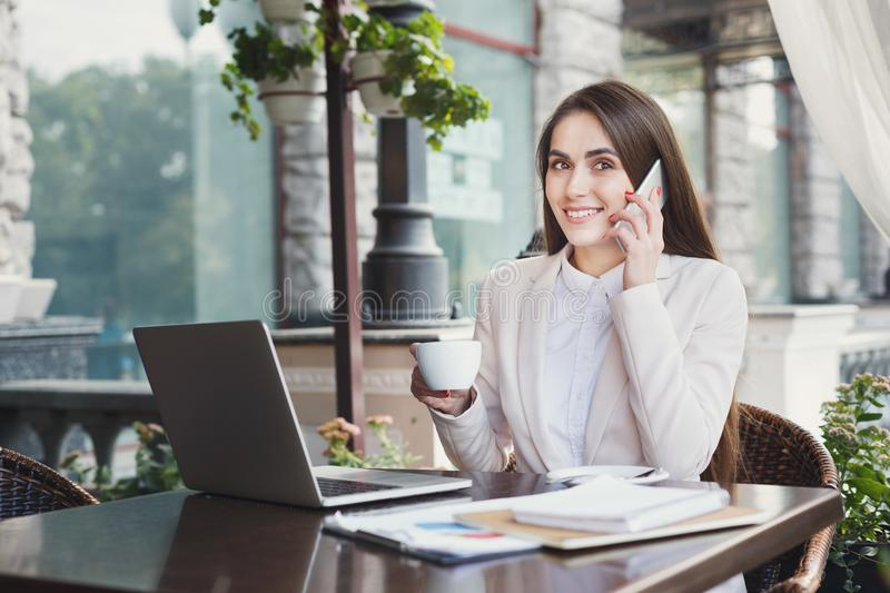 Young woman talking on phone and drinking coffee stock image