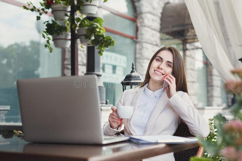 Young woman talking on phone and drinking coffee royalty free stock photography