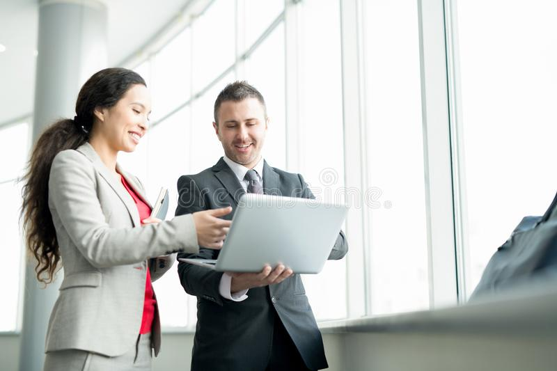 Smiling Businesswoman Talking to Colleague by Window royalty free stock images