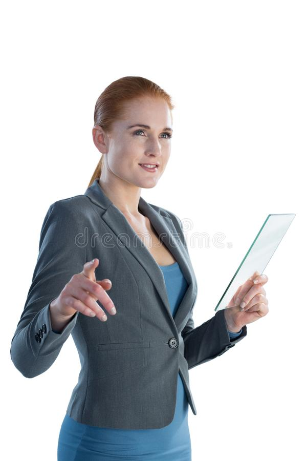 Smiling businesswoman touching on imaginary screen while using glass interface. Against white background royalty free stock photos
