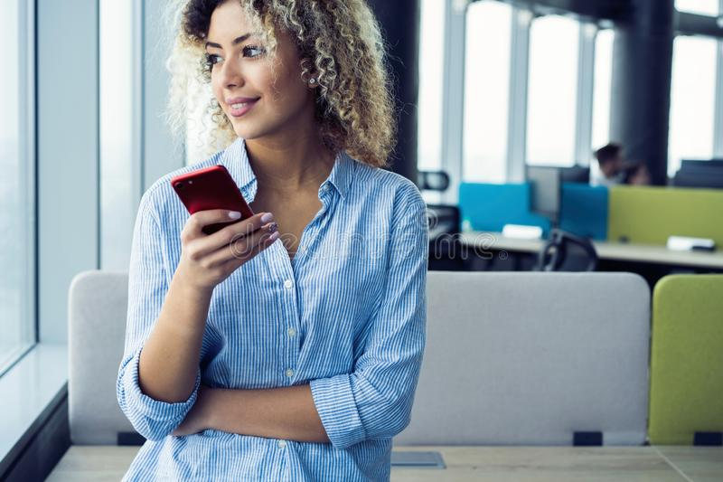Smiling businesswoman using smartphone in office. Wearing in blue shirt royalty free stock image