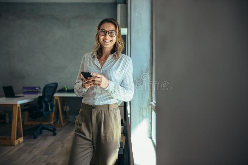 Smiling businesswoman at work in office royalty free stock photo