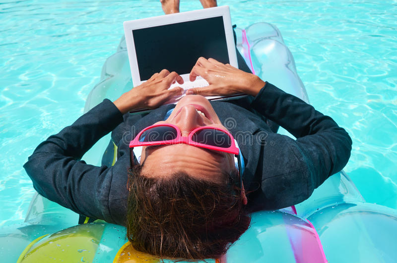 Smiling businesswoman working on laptop in pool stock photos