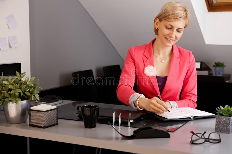 Smiling businesswoman working in office. Smiling young businesswoman sitting at desk in office, writing notes stock images