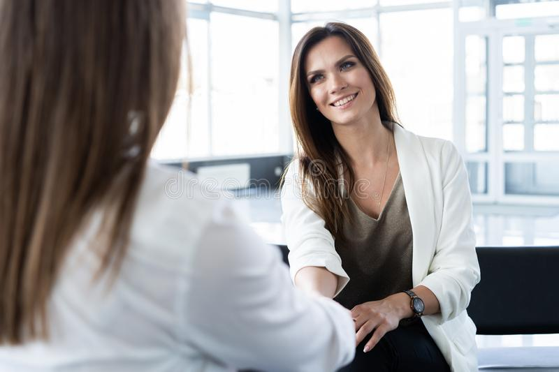 Smiling businesswomen colleagues handshaking in office, making deal at meeting, manager shakes hand of satisfied client. Smiling businesswomen colleagues stock photo