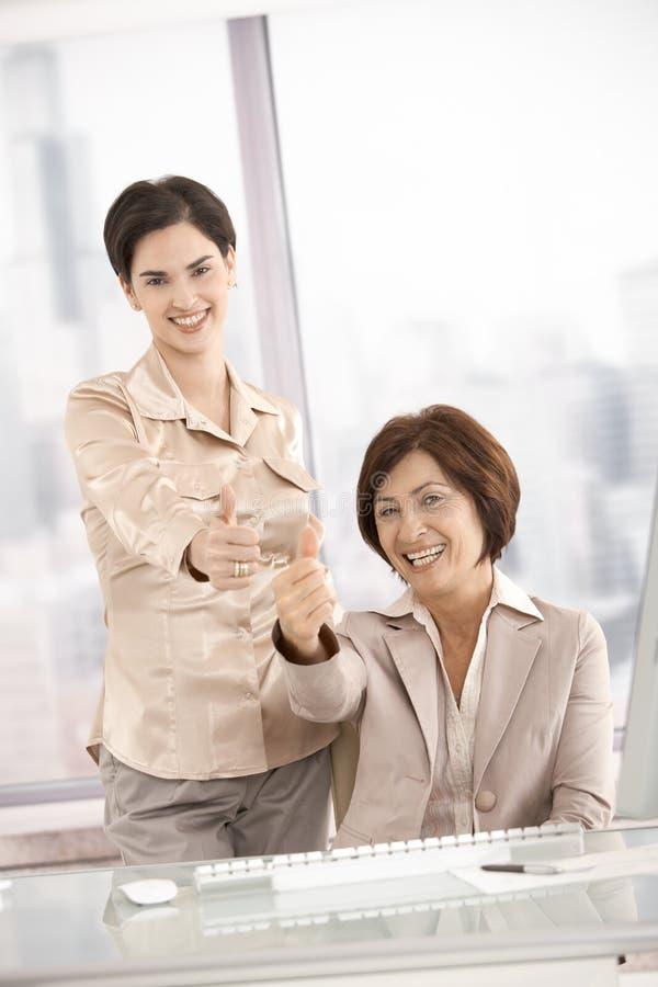 Smiling businesswomen giving thumb up stock photo