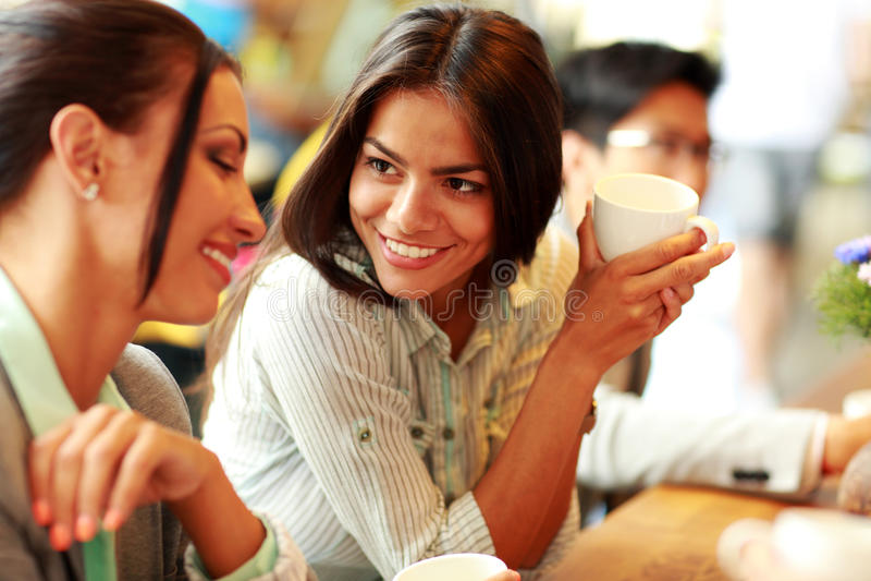 Smiling businesswomen having coffee break. Portrait of young smiling businesswomen having coffee break stock photography