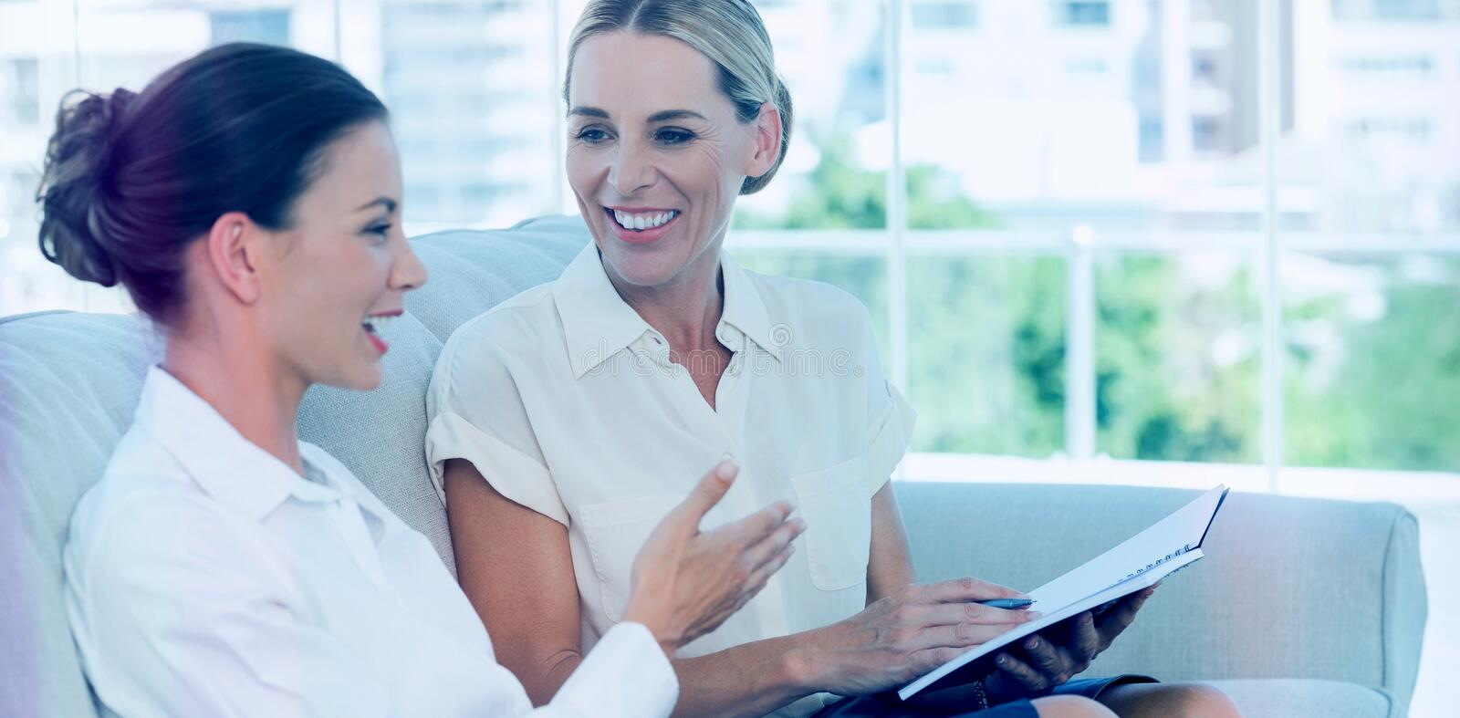 Smiling businesswomen talking and working together stock illustration