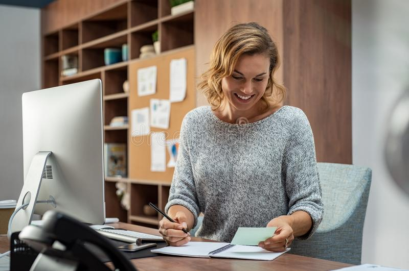 Happy business woman making notes royalty free stock photo