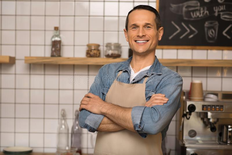 Smiling cafe owner with crossed arms. Portrait of smiling cafe owner with crossed arms standing in coffee shop royalty free stock photo